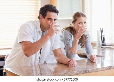 Young couple enjoying some milk in the kitchen