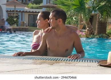 Young couple   enjoying the sun in the swimming pool