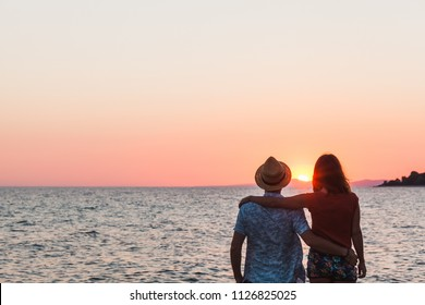 Young couple enjoying sunset by the sea