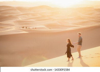 Young couple enjoying the sunset in dunes. Romantic traveler walking on the Sahara desert. Adventure travel lifestyle concept.
