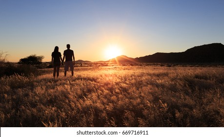 Young couple enjoying the sunset in the meadow.