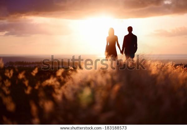 Молодая пара наслаждаясь закат в луг