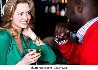 Young couple enjoying their weekend at bar, busy in romantic conversation.