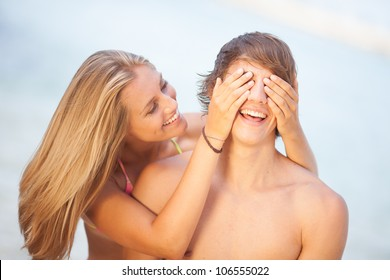 Young couple enjoying themselves at the beach covering eyes