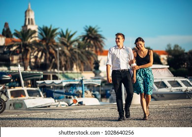 Young couple enjoying vacation time.Boyfriend and girlfriend having a romantic walk along the coast in a seaside town.Romantic weekend at he coastal city,holiday at the seaside.Relaxing walk at sunset