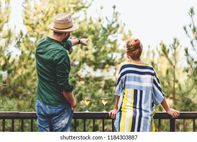 Young couple enjoying the view of nature from a balcony