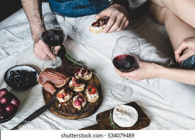 Young couple enjoying wine with italian antipasti snacks set: crostini, bruschettas, prosciutto, olives, grapes and cheese. Selective focus, desaturated. Valentines day, dinner, food and wine concept
