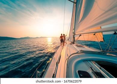 Junge Ehepaare segeln gerne bei Sonnenuntergang im tropischen Meer auf ihrer Yacht.