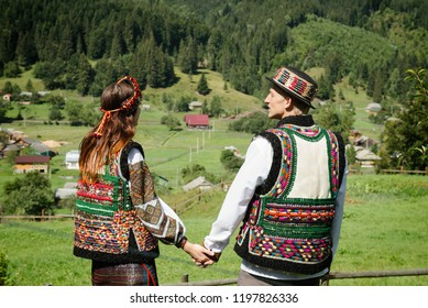 Young couple in ethnic and traditional Ukrainian clothes in the Carpathian mountains