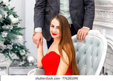 Young couple in evening outfits (jacket and red dress) in white christmas interior