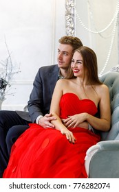 Young couple in evening outfits on the sofa in the white room