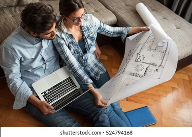 Young couple examining blueprints of they new house.Moving house concept.
