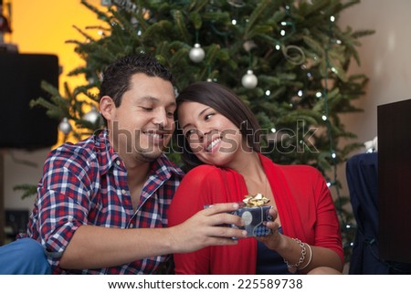 young couple exchanging christmas gifts and celebrating by the christmas tree
