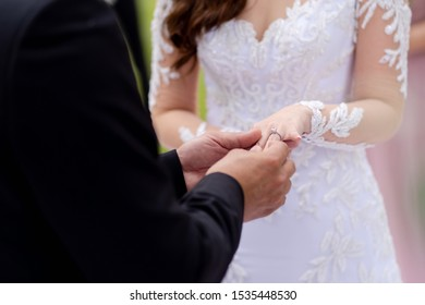 Young couple exchanging rings during wedding ceremony, closeup