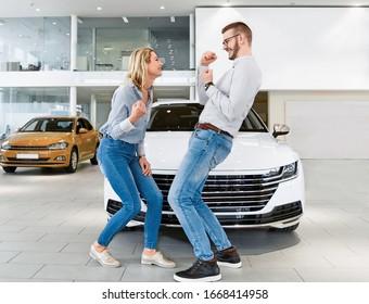 Das junge Paar begeisterte sich vom Kauf eines neuen Autos. Springen und Feiern vor dem Fahrzeug
