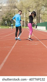 Young couple exercise running on the track