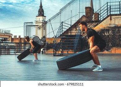 Young couple exercising on the roof of a building witht truck tire