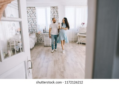 Young couple expecting baby standing together indoors