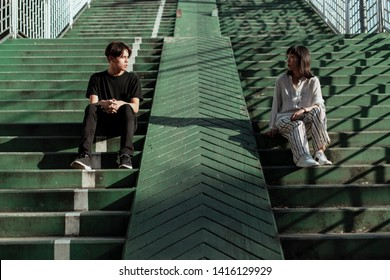 Young couple face to face, wearing black and white clothes sitting side by side on the green overpass stairs across street city