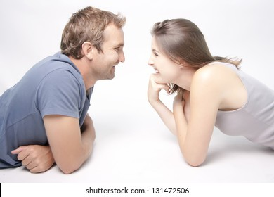 Young Couple facing each other smiling playfully