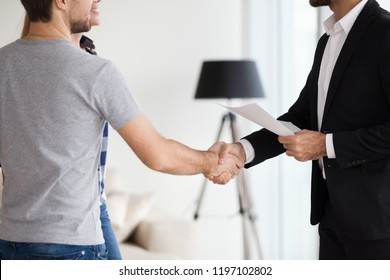 Young couple, family at meeting making deal, signing сontract with realtor, landlord, banker. Husband handshaking with man in suit. Concept of meeting with client, customer. Closes up