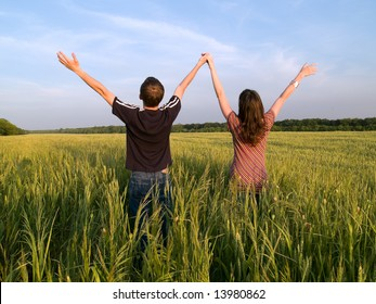 Young Couple in Field Holding Hands Up Rear View