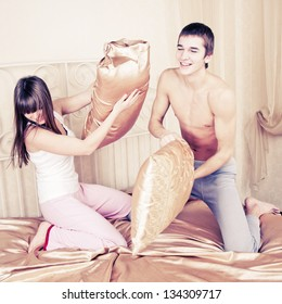 Young couple fighting pillows in the bedroom