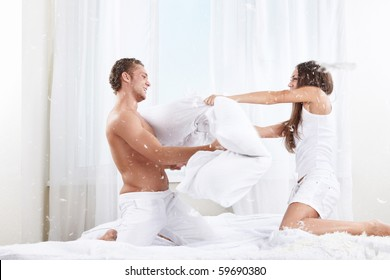 Young couple fighting pillows on the bed