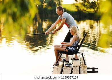 Young couple fishing on the pier at the river