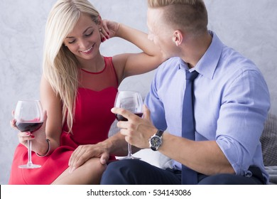 Young couple flirting and drinking wine on a bed