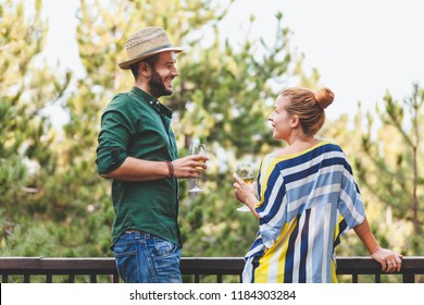 Young couple flirting on the balcony drinking white wine
