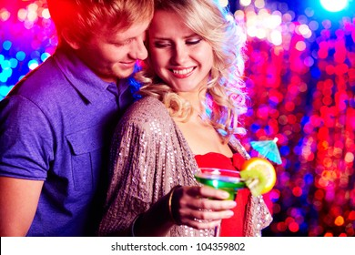 Young couple flirting at party against sparkling background