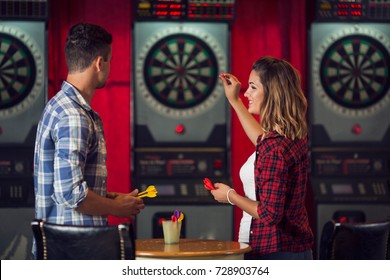 Young couple flirting and playing darts