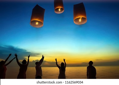 Young couple and friends lighting floating lantern on the beach in the twilight time celebrating their wedding on KohSamui Thailand