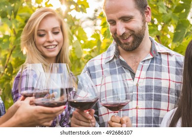 Young couple with friends tasting red wine outdoors in autumn vineyard.