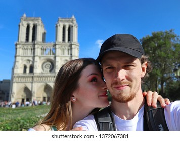 Young couple in the front of Notre Dame de Paris cathedral, France