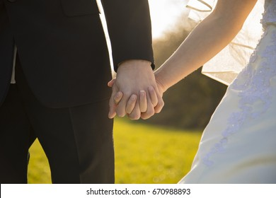 Young couple full of love at marriage hold their hands while sundown