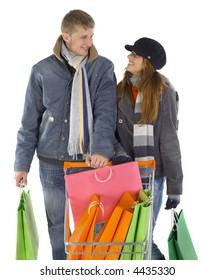 Young couple with full trolley. Smiling and looking at each other. White background, front view