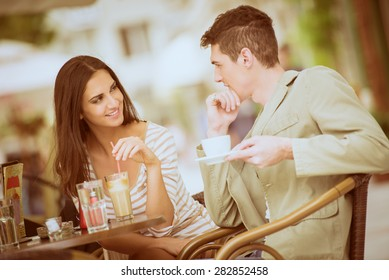 Young couple in garden cafe flirts and enjoys the coffee.