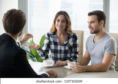 Young couple getting keys to new apartment from realtor. Family buys, rents new house. Customers or renters buy or rent real estate
