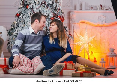 Young  Couple with gifts near the Christmas tree. Pregnant wife and husband  together during the Christmas holidays. Family romance New Year and  Xmas.