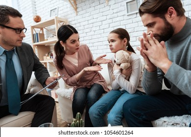 Young couple with girl discussing problems in family with family psychologist. Discussion of concern problems in family at psychologist office.
