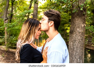 Young couple give their first kiss in a park at sunset, concept of falling in love.