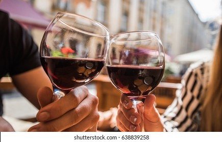 Young couple with glasses of red wine in a restaurant with city view