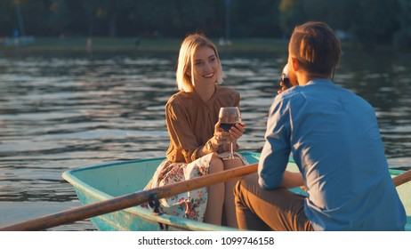 Young couple with a glasses of wine in a boat