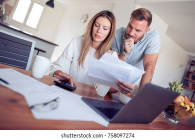 Young couple going through their financial records in the comfort of their home.