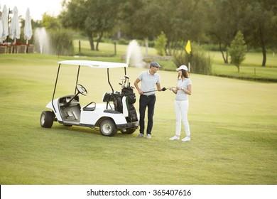 Young couple at golf cart