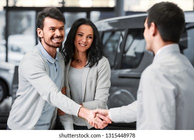 Young couple grateful sales manager for advice in auto salon.