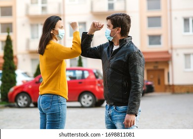 Young couple greeting with elbows. Social distancing concept. Man and woman wearing medical face mask. People maintain social distancing to prevent from virus spreading. Friends shaking elbows.