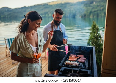 Young couple grilling fresh meat outdoors.
